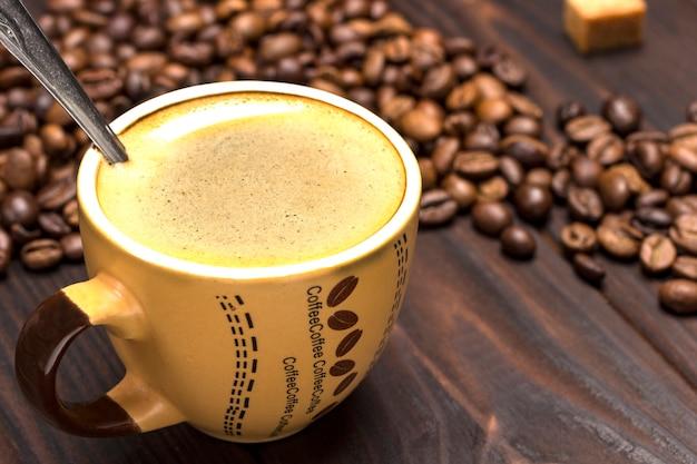 Xícara de café de perto. grãos de café na mesa.