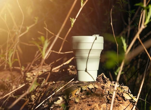 Xícara de café de silício reutilizável na floresta entre plantas verdes, árvores. estilo de vida ecológico.