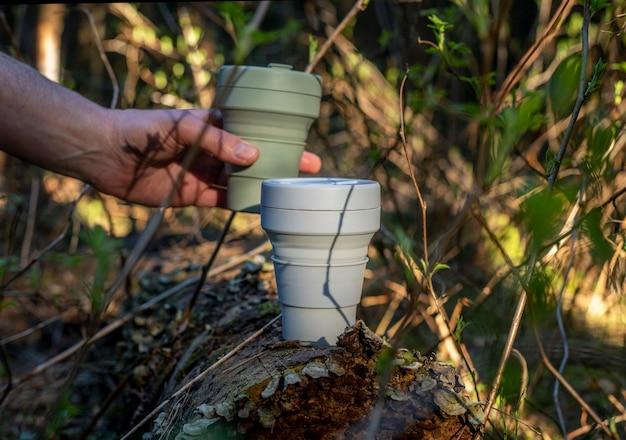 Xícara de café de silicone reutilizável ecológica na floresta levada por mãos masculinas entre árvores e plantas verdes. estilo de vida ecológico. bela luz do dia e sombras.