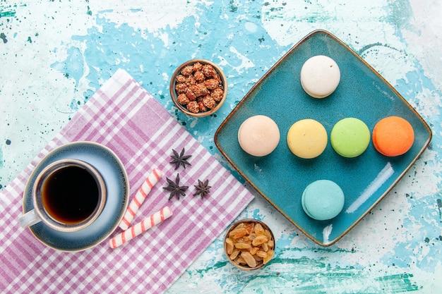 Xícara de café de vista de cima com macarons franceses, passas e confitures no bolo de superfície azul claro asse biscoito doce de torta
