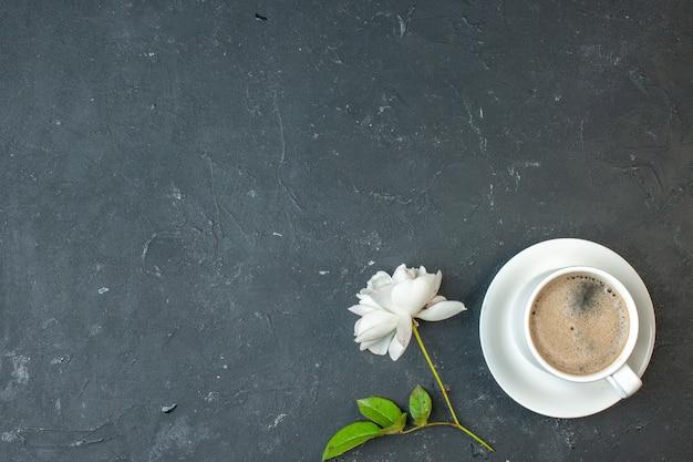 Xícara de café de vista superior com flor branca na mesa escura