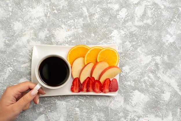 Xícara de café de vista superior com maçãs fatiadas, laranjas e morangos no fundo branco frutas frescas maduras