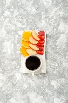 Xícara de café de vista superior com maçãs fatiadas, laranjas e morangos no fundo branco frutas maduras frescas maduras
