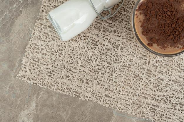 Xícara de café decorada com cacau em pó sobre superfície de mármore.