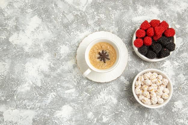 Xícara de café delicioso cappuccino com frutas na superfície branca