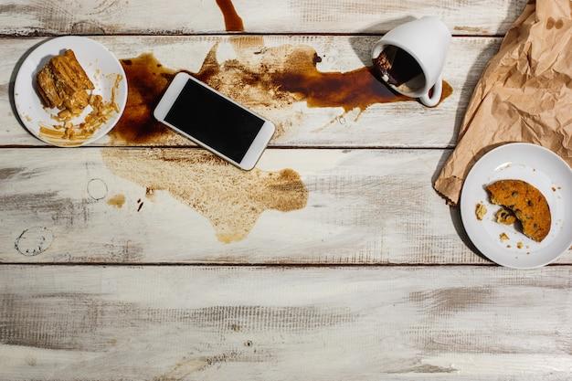 Xícara de café derramado na mesa de madeira