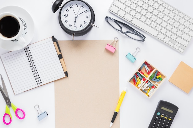 Xícara de café; despertador; teclado e material de escritório na mesa branca