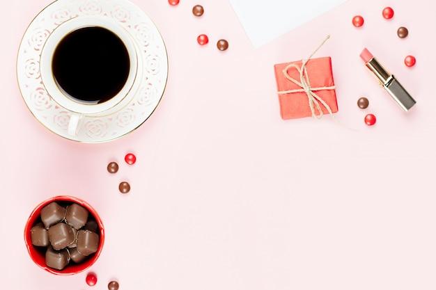 Xícara de café, doces de chocolate, caixa de presente plana leigos. fundo feminino.