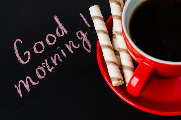 Xícara de café e biscoito em um fundo escuro.