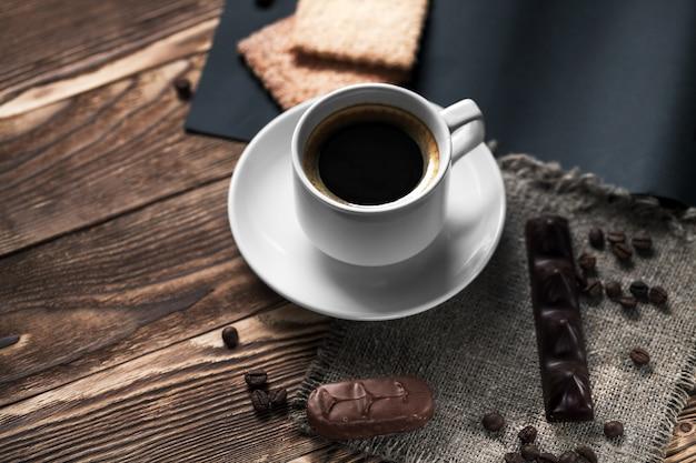 Xícara de café e biscoito na madeira