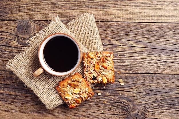 Xícara de café e biscoitos com nozes na mesa de madeira vintage