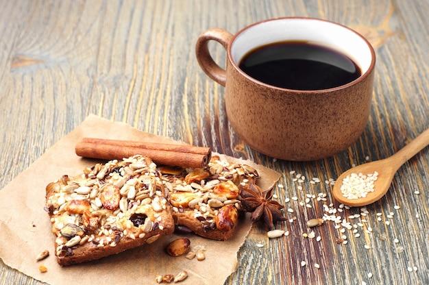 Xícara de café e biscoitos com nozes na velha mesa de madeira