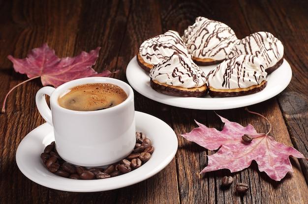 Xícara de café e biscoitos doces com creme na velha mesa de madeira