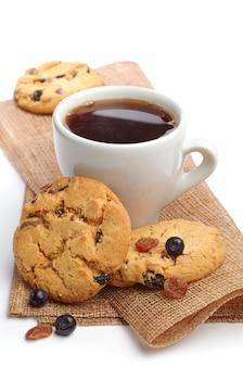 Xícara de café e biscoitos doces com passas e mirtilos