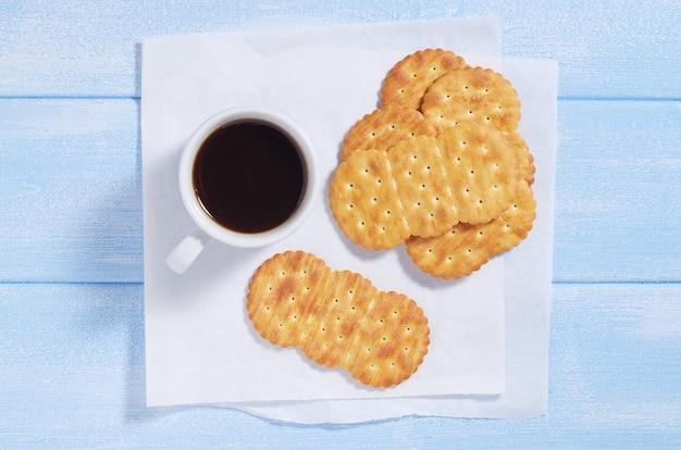 Xícara de café e biscoitos na mesa azul, vista de cima