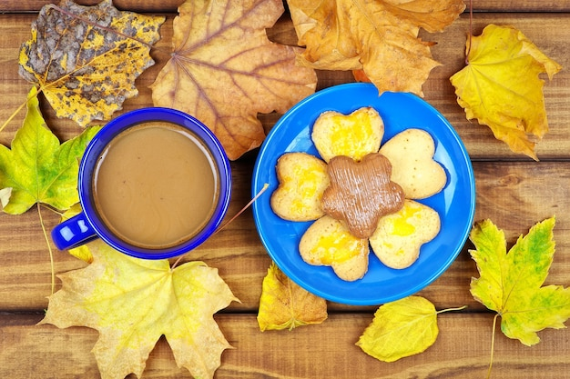 Xícara de café e biscoitos na mesa com folhas secas de outono. beber café no outono em mesa de madeira rodeada por folhas secas de outono