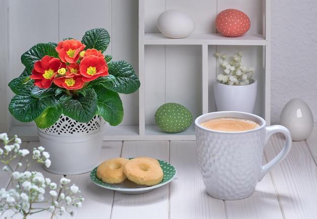Xícara de café e biscoitos na mesa de madeira branca com prímula vermelha e decorações de primavera
