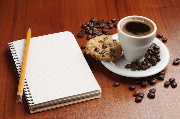 Xícara de café e bloco de notas aberto na mesa
