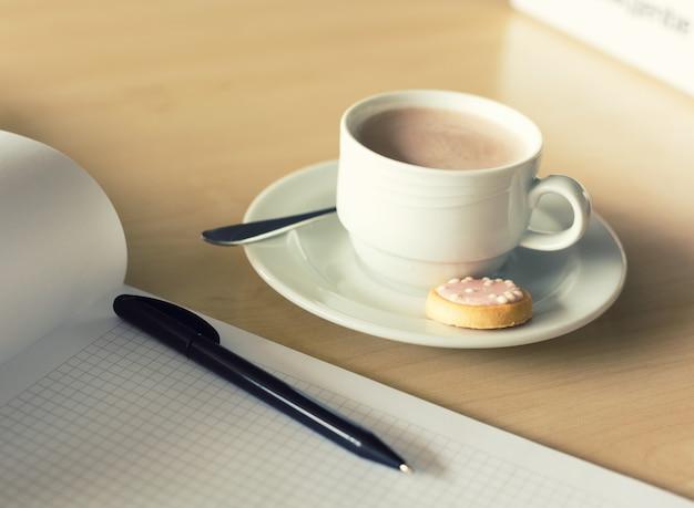 Xícara de café e bloco de notas com caneta