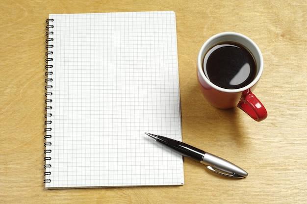 Xícara de café e bloco de notas em uma mesa de madeira