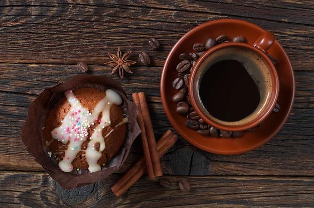 Xícara de café e bolinho na mesa de madeira escura, vista superior