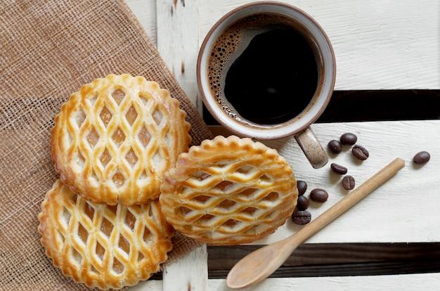 Xícara de café e bolos de treliça com recheio de maçã, vista de cima