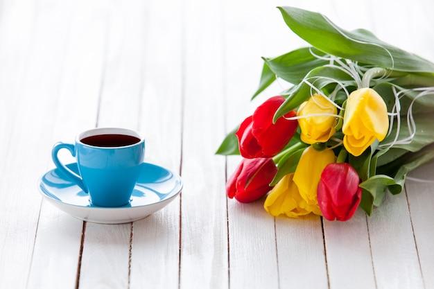 Xícara de café e buquê de tulipas
