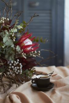 Xícara de café e buquê exótico sem embalagem fica na mesa com toalha de linho bege, conceito de manhã de férias