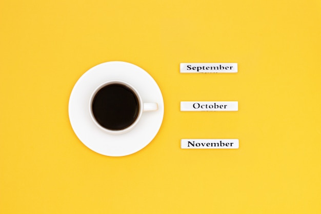Xícara de café e calendário de novembro outubro de setembro no fundo amarelo