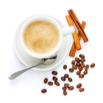 Xícara de café e canela no fundo branco
