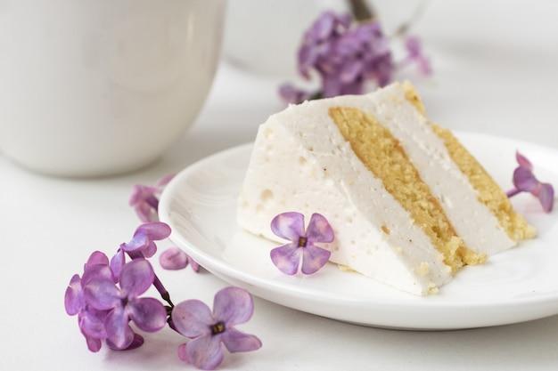 Xícara de café e chifres de bolo da vida ainda com um buquê de lilases sobre uma mesa branca, uma xícara de café, um prato com um pedaço de bolo. dia internacional da mulher, 8 de março