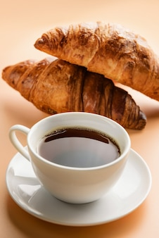 Xícara de café e close-up de croissants.