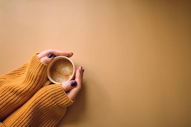 Xícara de café e com a mão de mulher no suéter amarelo