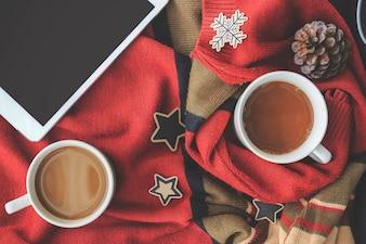 Xícara de café e computador tablet no fundo da camisola vermelha