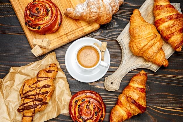 Xícara de café e croissant em fundo de madeira
