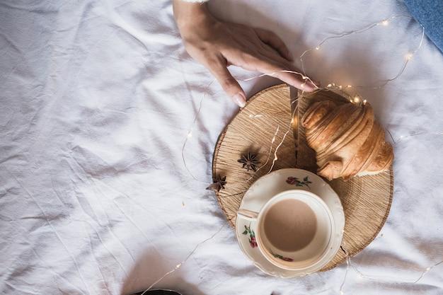 Xícara de café e croissant na bandeja de madeira