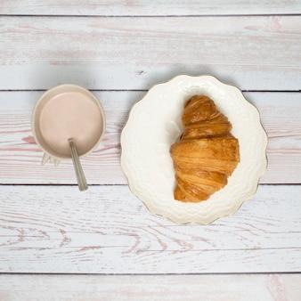 Xícara de café e croissant na placa cerâmica sobre a mesa de madeira
