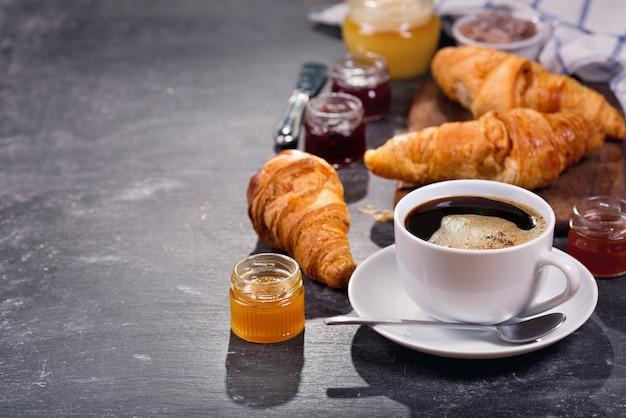Xícara de café e croissants com geléia de frutas na mesa escura