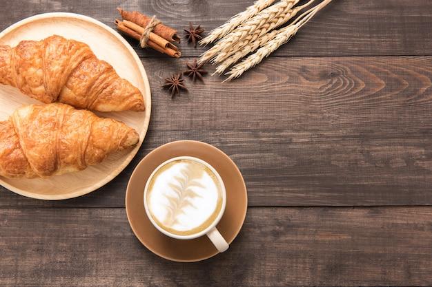Xícara de café e croissants cozidos frescos em fundo de madeira. vista do topo