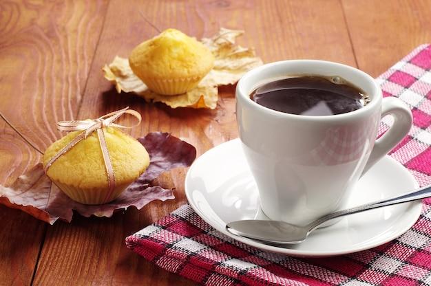 Xícara de café e cupcakes na mesa de madeira