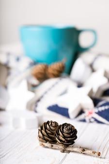 Xícara de café e decorações de natal e saliências em primeiro plano