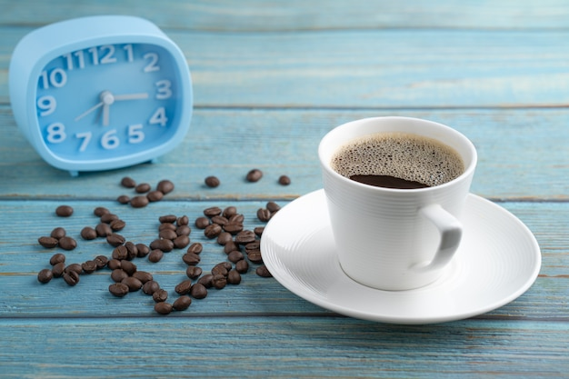 Xícara de café e despertador azul na mesa de madeira.