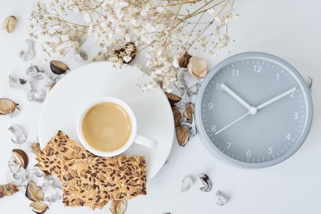 Xícara de café e despertador clássico na mesa branca
