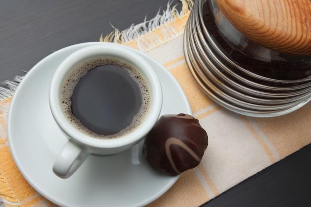Xícara de café e doces de chocolate na mesa