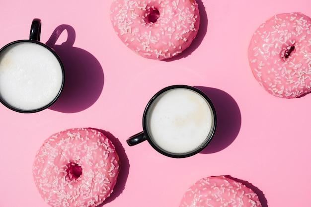 Xícara de café e donuts no fundo rosa