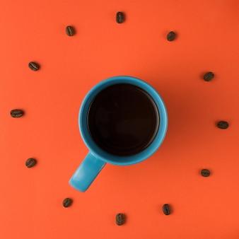 Xícara de café e feijão assado dispostos como face do relógio, vista superior. hora do café. ideia interessante conceito de energia e refresco.