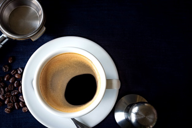 Xícara de café e feijão com equipamento para café