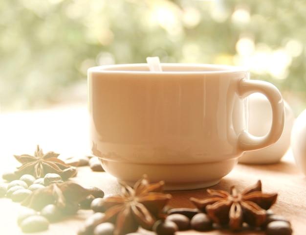 Xícara de café e feijão com fundo de folha verde turva