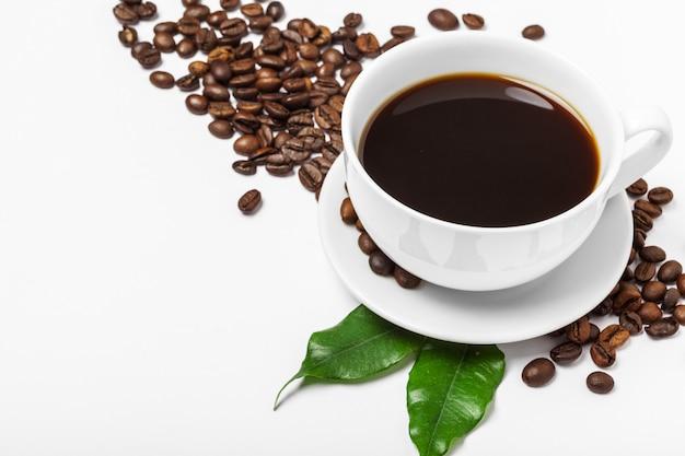 Xícara de café e feijão em um branco