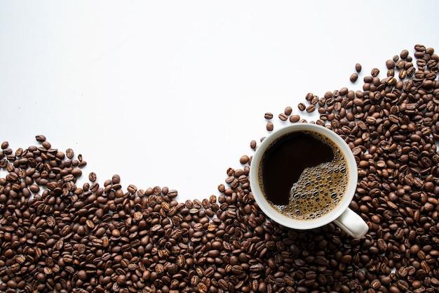 Xícara de café e feijão na mesa branca